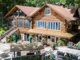 This charming, vintage 1939 full log home has been updated & equipped with every convenience & luxury you can imagine! The Main home features 5BR/2BA's, a floor to ceiling fieldstone FP in the Living room, commercial grade appliances in the kitchen, & a large entertainment addition complete w/bar & gorgeous views of crystal clear Smoky Lake. For amusement, younger folks will delight in the game room, & the adults will appreciate the billiard room. For family & friends that will visit, there is a 3BR/1BA guest cottage offering privacy & ample sleeping quarters. The estate is situated on 22.3 acres, faces west for breathtaking sunsets and has 700' of sandy swimming frontage. The grounds are beautifully landscaped & there is a large garage w/workshop, a blacktop drive, pole building, wet boathouse & permanent pier at the waterfront. Well maintained, pride of ownership is evident with this fine property. Video: http://tour.circlepix.com/home2/HMVVND/451-SMOKY-LAKE-DR-Stambaugh-MI-159036