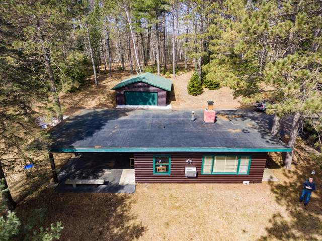 "A great place to make family memories awaits on crystal-clear, no public access, exclusive Carlin Lake. This ""neat-as-a-pin"" 2 bedroom/1 bath home is one of just two condos which share 12 acres of wooded land and 424' of beautiful sand frontage. Beautiful log siding outside, lovely pine paneling inside, and a fieldstone fireplace with pellet insert assure a beautiful Northwoods experience all seasons of the year. A huge picture window affords a commanding view of the lake and two large bedrooms assure sleeping room for the whole family. Outside you have your own dock and pier, and as a roomy 529 sq. ft. detached 2-car garage to keep all your Northwoods toys. An 18x28 carport gives you a great place for your car or boat, or even use it as a shaded area from which to relax and enjoy the lakefront. Move-in ready and furnishings are negotiable. Condo agreement allows for occasional rentals to supplement your income and make this an even better investment. Come see today!"