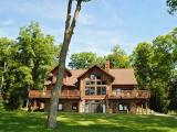 The North and South setting of this elegant, spacious, yet comfortable custom-built home on two hundred feet of level sandy beach gives one the most expansive views of beautiful Lake Lucerne. You will be delighted with the gourmet designed kitchen, which features high-end rustic cherry cabinets, granite counters, two hammered copper sinks and Wolf / SubZero appliances. The laundry/office, half-bath, walk-in pantry, covered grill area and a two stall garage with in-floor heat are located just off the kitchen. There is Maple flooring throughout and gorgeous Travertine tiles in the laundry, baths and walkout level. Your feet will be toasty warm when you step out of the shower onto heated floors in the baths. This home has two master suites. A large walkout lower level comes fully finished with a stone fireplace, full bath, exercise room and kitchen.