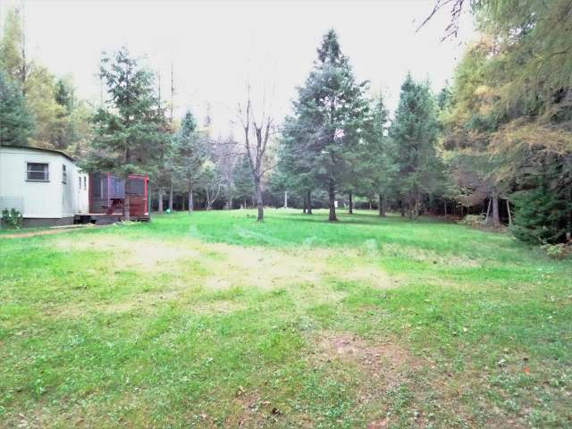 40 Acre Wooded Hunting Parcel in Ashland County with 3 food plots, 2 ground blinds and 3 ladder stands and adjacent to forest and farmland. Off grid 2 bdrm 14x50 mobile home is generator ready, heated by woodstove and comes furnished for your hunting camp and sits on the south east corner just off the gated easement road. Great views over a mowed clearing from the 10x32 treated deck with screenroom. Equipment shed, generator room, privy and covered firewood storage. Hiking and ATV trails through the mixture of high and lowland is wooded with aspen, evergreen, black spruce and tamarack. Close to the Chippewa River and within minutes of County and National Forests. Remote location approx 15 miles north of Park Falls off of Hwy 13 in Peeksville just east of Glidden. Abundant wildlife for your viewing and hunting pleasure. Game cameras have captured a large bear, nice buck, lots of does and a strutting male turkey so far this year.