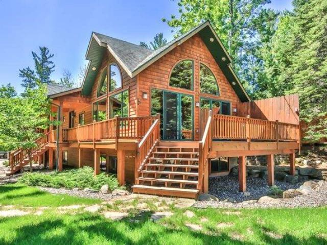 """TOMAHAWK LAKE SANCTUARY. Exclusive property on the Minocqua Chain. 302' of frtg lends seclusion along with a wildlife safe haven. Paved walkway leads to inviting covered porch entry of this custom built executive home. Every aspect reflects detail and planning to provide the optimum in Northwood's family living & entertaining. Panoramic views and floor-to-ceiling fieldstone FP in great room. Master suite has tray ceiling, walk-in closet and bath w/tiled shower. Comfortable LL family rm w/fieldstone FP & wet bat. Two addt'l BR's & full bath offers privacy for family or guests. Some of the numerous features include; wood flooring, knotty pine T&G, log railings, 8"""" custom panel door, decks, impeccable landscaping, zoned irrigation system, large perm. pier, boathouse w/sun deck, att. garage plus 3 car det. gar with finished bunkroom above. This distinctive home will provide a proud living experience for the discriminating buyer. Features list avail."""