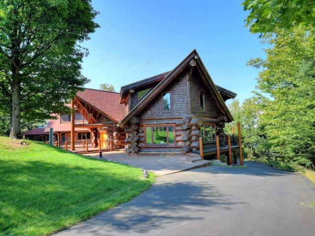 "You will say ""Wow"" when you see this Custom Built Full Log Home with a spectacular spiral staircase and 985 feet of frontage on a crystal clear lake & 7 acres of privacy! This home has breathtaking views from a wall of windows overlooking the lake, a beautiful stone fireplace and a well equipped kitchen with high end appliances, hickory cabinets & granite countertops. Maple flooring compliments the logs and floors on all levels are heated for your comfort. Unique walkway on upper level leads to a master bedroom suite with balcony on one end & three bedrooms & a full bath on the other. The lower level family room has patio doors to the lake, two guest bedrooms, laundry room plus extra storage. Enjoy a summer evening in the gazebo or soak in the hot tub. Plus you have room to store all the toys with a large garage with storage above, a 42 X 49 building with heated floor, a 30 X 50 building & a storage building at the lakeside. Take a look so you can say ""Wow"" too!"