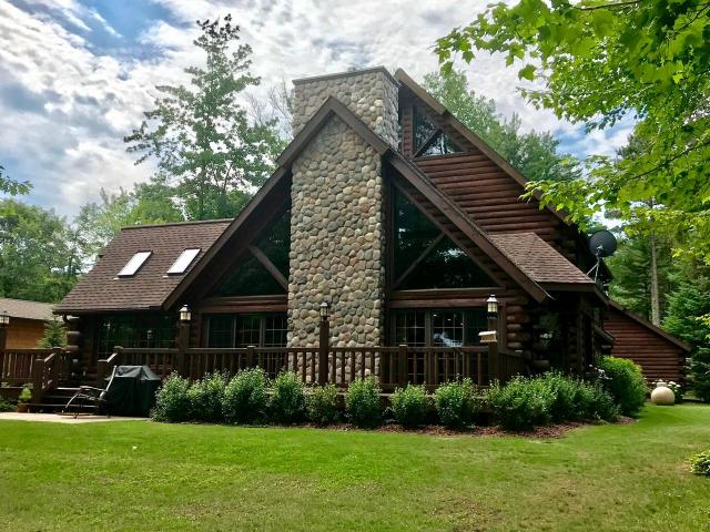 Located off of the desirable Seven Oaks Ln this Tomahawk Log home comes w 3 BR, 4BA, and 3,650 sq ft. No detail was left out when it came to designing this home from the towering 22' ceilings, hrdwd flring, flr to ceiling lakeside windows, & high end finishes throughout. Main floor you will find master BR w/ ensuite, laundry, huge kitchen, living rm w/fireplace, & cozy lakeside den. Upstairs there are 2BR's w/ 22' ceilings, full BA, & loft/office. Basement there is a 4th nonconforming BR, another full BA, & sprawling rec rm. Seller has many updates being installed first week of June. Updates include: new granite in kitchen, powder room, and laundry room, all new high-end appliances, hardwood floors refinished, new carpet, exterior deck stained, & ceiling tiles replaced. Home also has in-ground sprinkler system, security system, & central A/C. Located on 100' of level, sandy frontage w/ western sunset views and just 8 steps to the lake. There is a det. 2 car garage w/ extra storage.