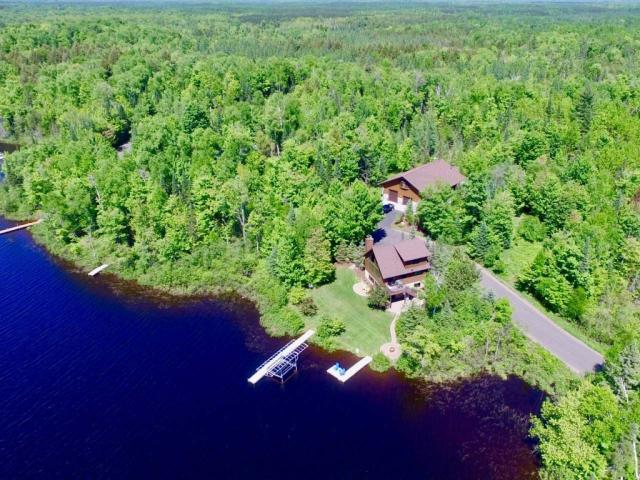 Cedar log & stone sided Chalet Style home w/3,300+/-sqft Guest House & Man Cave Garage! The best set up in the Northwoods with amenities & beautiful finishing details on a level lot w/western facing 316' sand frontage. No detail was left out in this 3BR 2BA home and 2BR 2 BA Guest House/Garage. Towering cathedral ceilings, floor to ceiling windows, custom FP, granite counters, Alder cabinets & Sub-Zero/Wolf appliances. Main level master BR w/master bath. The master BA walk-in shower w/8 shower heads & lrg soaker whirlpool tub. In the upper left, find a BR/Office w/balcony. Spacious walk-out basement w/many windows facing the lake. This house has it all: 50 year Elk Shingles, Snow Load Roof, Blacktopped Driveway, Central A/C, In-Floor Hydronic Heat, In-Ground Sprinkler System, Maximum Security System, High-Speed Internet, Polymer Decking, Surround Sound System throughout the home, Outdoor Speakers System!