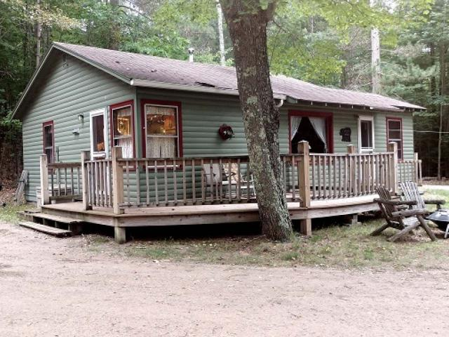 Want a spot on the Three Lakes Chain? Here it is. Charming 2BR/1BA seasonal cabin with newer furnace in deep crawl space, great sandy water frontage. Sandy for sure. Faces West for great sunsets. Only $550 a year for condo fees. There is a wood burning stove,new kitchen sink and cabinets.Furnishings stay except for one cabinet . Nice composite wrap around deck. Very Northwoodsy and location is so great. Enjoy the Northwoods out on your pier with family and friends.