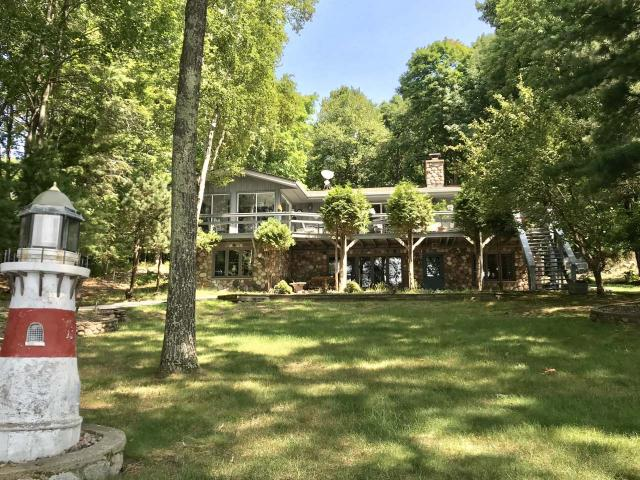 """Fabulous home on the """"King of Lakes"""" part of the Minocqua Chain. Beautiful home with 2 car attached & 2 car detached garages. You will love the gentle slope to the sandy beach and permanent pier where you will see beautiful sunsets. This amazing property faces southwest on Lake Tomahawk. The yard is fully landscaped, with paved driveway. Property is beautifully cared for & meticulously maintained. This Home features cedar siding & real fieldstone trim around the entire home. This home has been updated throughout. New roofs, appliances, granite counter tops, tile floors & furnaces in 2010. The master suite has sliding patio doors to the deck & a newly remodeled master bath. The signature fieldstone wood burning fireplace will keep you toasty warm. The Kitchen/Dining room opens to a beautiful sun porch that is yr-round. The Large wrap around deck with benches is a great gathering place. The lower level with walkout features another wood burning brick fireplace & lots of storage space."""