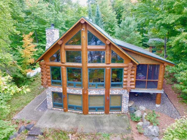 This one-of-a-kind full log home on Carlin Lk features hand-scribed white pine logs & an interior that's been tastefully finished with Northwood's decor. Offering 4BR & 3BA's w/200' of sandy frontage, this property has everything you look for in a Northwood's retreat. The drive in will remind you of a Swiss village with horizontal logs, cedar shake siding & nice landscaping There's also a 2-car detached garage to match. Inside you'll notice hard-surface countertops & floors, full baths on all 3 levels & a large water view from almost every room in the house. The master ensuite is upstairs, but there is a large main-level BR with a full bath off the entrance that could easily be used as a master. Additionally, there are 2 more BR's on the LL. The basement has a walkout w/add'l sq. ft. that could be finished into another room. There are gradual steps to the water & a firepit area by the pier that creates a great setting for campfires. Come see this amazing property before it's too late.