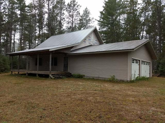 UNFINISHED GEM!! This 2,242 sq ft unfinished home with 3-car attached garage has incredible potential. The parcel as over 800 feet of frontage on the Brule River, a world-class trout fishing destination, and 10.1 acres of wooded and cleared land. The structure has vinyl siding and a metal roof for easy maintenance and installed septic and a drilled well. Snowmobilers will be happy to know that the trail goes through part of the parcel! The property also comes with a 2,355 sq ft bar/ restaurant with additional living quarters and outbuildings that can be used for your next business venture or as extra residence/ storage.