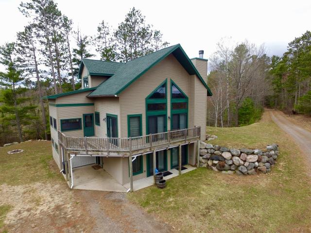Minocqua Chain Chalet & Boathouse! Spacious 3BR, 4BA hm on Lk Kawaguesaga with over 500' frontage. Located in a very private area for those looking for some peace & quiet yet wanting to be on one of the most sought after lake chains in the Northwoods. Main floor is open concept w/gas FP, cathedral ceilings, floor to ceiling lakeside windows, & lrg lakeside deck. The updated kitchen features Quartz countertops, breakfast bar, farmhouse sink,& stainless steel appliances. There is a main floor master BR w/ ensuite & att'd 3 season porch. The 3rd bedroom is in the upstairs loft, & has been completely renovated w/ new stainless steel rails, flooring, walk-in tiled shower,& Juliet balcony. The walkout basement features a wood-burning FP, rec room, wet bar, & lots of natural light. This home has all the bells & whistles from new Generac Generator, buried 1000 gal propane tank, central A/C, in-floor heat, auto-lock Schlage doors, & att'd garage. Come see this spectacular property today!