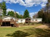 2 HOMES FOR THE PRICE OF 1! Here you will find 2 homes situated on 1.67 acres & 125' of level frontage. The main home has 4BR, 2BA, spacious living quarters, laundry, & lakeside deck. The 2nd home consists of 1 master BR w/ensuite, spacious living qrtrs, laundry, & lakeside deck. You can live in one home & keep the other for your overnight guests or rent it out for add'l revenue. Underneath the 2nd home there is add'l garage space w/ 2 overhead doors w/ enough space to store boats, RV, snowmobiles, etc. In addition there is a 3 car att'd garage which connects to both homes. Each home has its own forced air A/C & is furnished with its own appliances. This yard was meant for entertaining, huge lakeside deck, level yard for volleyball, bonfire pit w/ wood storage shed, & another outbuilding for toys. Enjoy your western sunset views overlooking undeveloped land. You are centrally located in the heart of the ATV/snowmobile trail system and just a boat ride away from many restaurants/bars