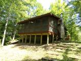 """Here is a magical 2 bedroom cottage (could be year round). Features include carpet/tile and laminate flooring, individual cedar plank paneling, wood burning fireplace, bath with shower, convenient kitchen open to the 15 1 /2 x 16 1/2 living room with patio doors leading to a 8 x 22 screen porch overlooking Squaw Creek. The property has a 6"""" drilled well and a fairly roomy concrete block crawl space foundation with hot water tank and well water pressure tank. In addition, there is a 24 x 24 garage with automatic door opener and a wonderful pier. This property is located in the Chequamegon National Forest and fronts on Squaw Creek that is navigable to 736 acre Squaw Lake which is a full recreation, excellent fishing lake. What a desirable property and location for an outdoor enthusiast."""