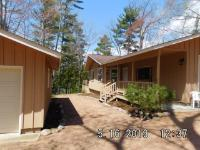 3BR 1.5BA on wooded lot with fieldstone fireplace, huge trex deck and western exposure. Lots of storage for toys, with 2 garages dry boathouse with track system and party room. Great neighborhood close to state land and snowmobile trail. On private dead end road.