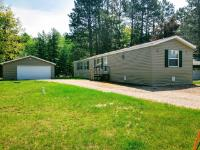 """AFFORDABLE ACCESS TO THREE LAKES CHAIN!!! If you are looking for easy, affordable access to the chain you have found your destination. This 3BR 2BT home is located on a channel that leads to Big Lake on the Three Lakes Chain of Lakes. All improvements have been made in the last 5 years! Recent updates include a new septic and well, new windows, doors and siding with an extra 1"""" insulation added to the existing 6"""" walls, and a new two-car garage for boat and other storage. The master bedroom and bathroom have also been recently remodeled. There is a boat launch right down the road, and snowmobile and ATV enthusiasts won't have to go far to hit the trails. Downtown Three Lakes is a short drive away as well. Start living your dream today!"""