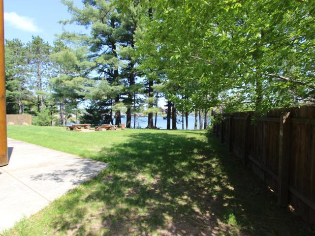 Live your Northwoods Dream in this quality condo located in walking distance to Downtown Minocqua. This lakeside end unit offers ultimate privacy with a large green grass yard out your patio door. Great lake views to enjoy all day sun or catch an evening sunset. This unit has high end finishing with quartz counter tops, six panel doors and elegant hardwood floors. Lake Minocqua offers endless recreation with over 1300 acres of water to enjoy. This unit is a great investment opportunity with the ability to rent weekly. Come enjoy maintenance free on Lake Minocqua!