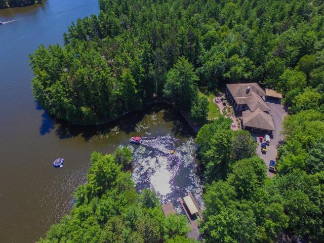 BayStoneManor.com ~ The epitome of Northwoods luxury on over 7.5 acres and 1200 ft of frontage on beautiful Yellow Birch Lake, which is located on the largest fresh-water chain in the world just minutes from downtown Eagle River. The main home has two levels and looks to be inspired by the famous Frank Lloyd Wright; showcasing modern angles and custom stonework with plenty of windows throughout. The interior is breathtaking and has two levels that have been custom-built. It offers 5 spacious bedrooms, 6 full bathrooms, multiple fire places, 2 offices, 2 full kitchens, 2 spacious dining areas, several sitting areas, a sauna, a bar, and a 3-car attached garage with 8' and 10' doors. Additional unique features include: a built-in BBQ grill and refrigerator on the outdoor patio, a 120 ft2 kids play house, a hot tub, a very comfortable sitting area with a outdoor Kiva (fireplace), a boathouse, a large insulated garage, another garage that is set up as a game room for kids and much more!
