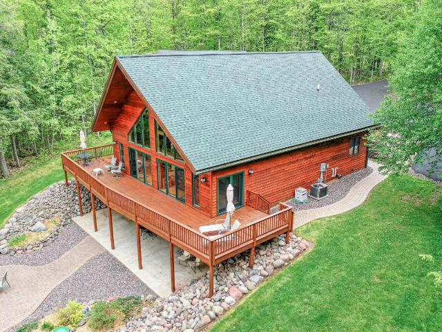 Premium 4BR/3BA West Shore Lake Gogebic executive home w/220' of prime frontage! Enter to find a massive great room w/towering cathedral ceiling, open kitchen/dining area, impressive fieldstone fireplace, huge log beams, large bedroom, full bath, laundry room, & commanding view of the lake through a wall of trapezoid windows. Go up the log staircase to find a loft suite w/master bedroom, en suite full bath + garden tub, abundant closet space, & mezzanine overlooking the great room. Downstairs in the charmingly finished walkout basement, there's an incredible family room w/ masterfully crafted wet bar, 2 large bedrooms (one with a walk out to the lakeside patio), storage rooms, & a full bath. Enjoy the lake's magnificence from the huge wraparound deck or lakeside patio w/fire pit or the included boat house, dock & boat lift. A blacktopped driveway w/extra parking is framed by beautiful landscaping while the 4-car detached garage offers plenty of storage for vehicles & toys.